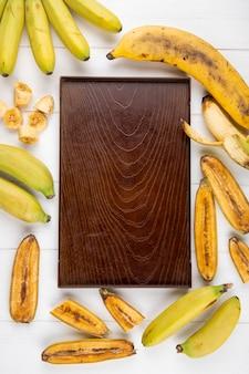 白の周りに配置された新鮮なスライスしたバナナと木の板の上から見る