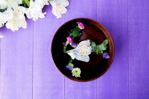 木製の紫色の背景に水とスターチスと白い色のアルストロメリアの花で満たされた木製のボウルのトップビュー
