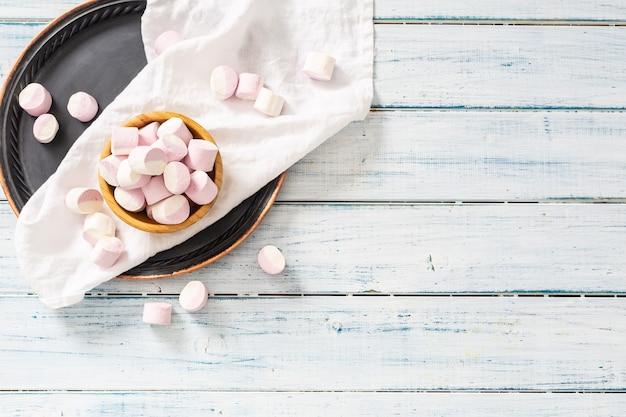 ピンクと白のマシュマロでいっぱいの木製ボウルの上面図。白いテーブルクロス、黒いトレイ、白い木製の表面にいくつかが散らばっています。