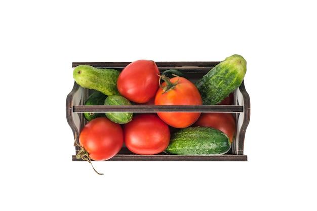 잘 익은 토마토와 오이 흰색 배경에 고립 된 나무 상자의 상위 뷰.