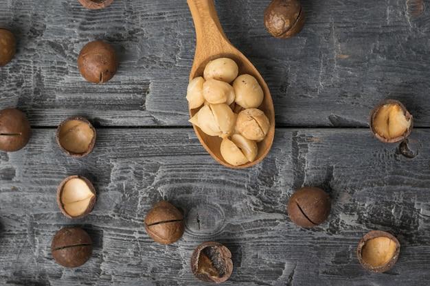 木製のテーブルの上に皮をむいたマカダミアナッツと木のスプーンの上面図。スーパーフード。