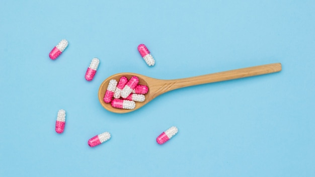 赤と白の薬のカプセルと木のスプーンの上面図