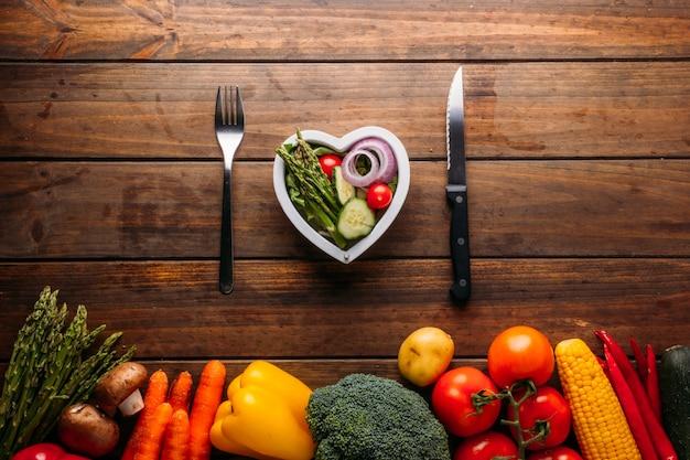 하트 모양의 샐러드 접시와 칼 붙이가 있는 나무 테이블의 위쪽 전망