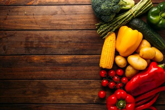 이미지 오른쪽에 여러 종류의 야채가 있는 나무 테이블의 위쪽 보기