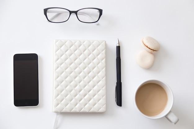 ノートパソコン、電話、コーヒーを備えた作業机の上面図
