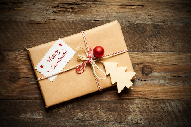 나무 표면에 메리 크리스마스를 읽는 카드와 함께 포장 된 크리스마스 선물의 상위 뷰