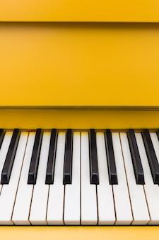 고전적인 흑백 건반이 있는 노란색 피아노의 상위 뷰