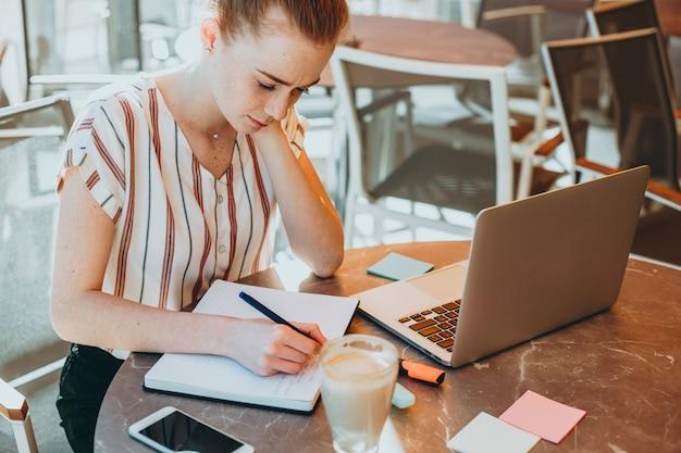 彼女のテーブルにラップトップを持ってコーヒーショップで屋外のノートにメモを取っている赤い髪とそばかすを持つ若いビジネスウーマンの上面図。