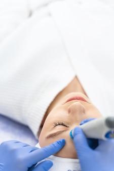 Вид сверху молодой пациентки, лежащей с закрытыми глазами во время процедуры красоты