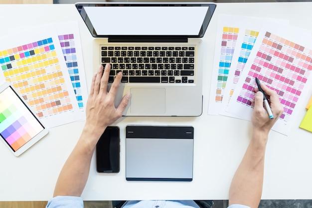 데스크톱 컴퓨터에서 작업하고 일부 색상 견본, 상위 뷰를 사용하는 젊은 그래픽 디자이너의 상위 뷰.