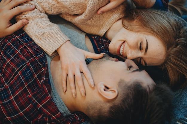 朝、自宅でキスする前に笑顔でベッドに寄りかかっている若い素敵なカップルの上面図。
