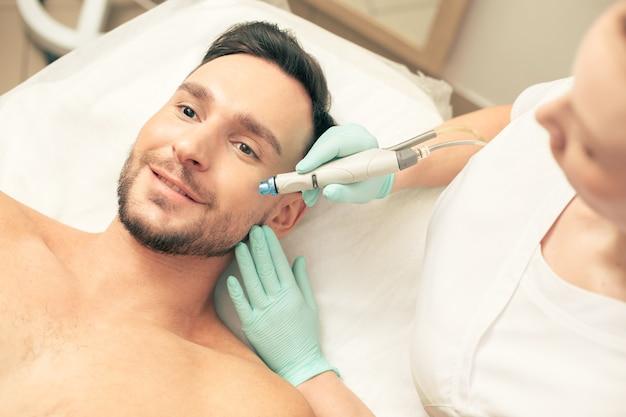 Вид сверху на молодого человека, выражающего радость, лежа на подушке, и косметолога, ухаживающего за кожей на щеке с помощью современного устройства