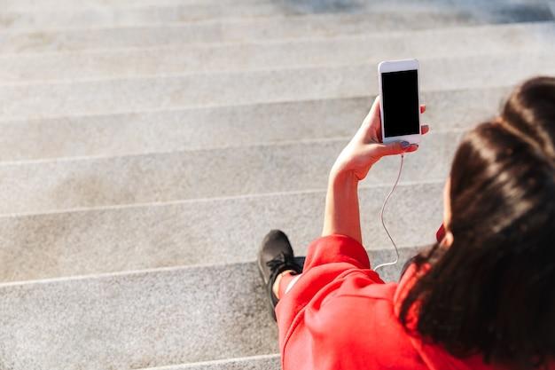 携帯電話を持って、イヤホンで音楽を聴いて、水を飲む若いスポーツ選手の上面図