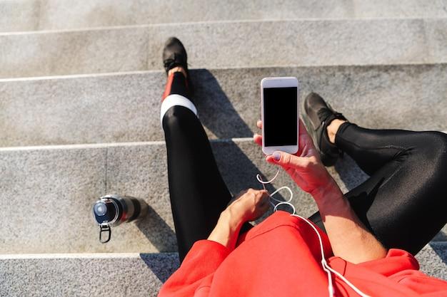 Вид сверху молодой спортсменки, держащей мобильный телефон, слушающей музыку в наушниках, питьевой водой