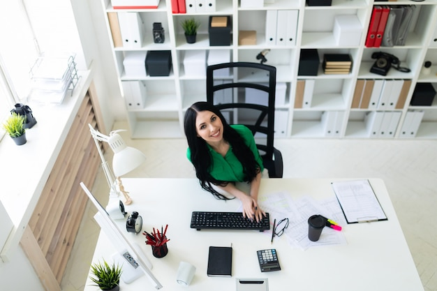 Взгляд сверху молодой женщины сидя на столе офиса и печатая на клавиатуре.