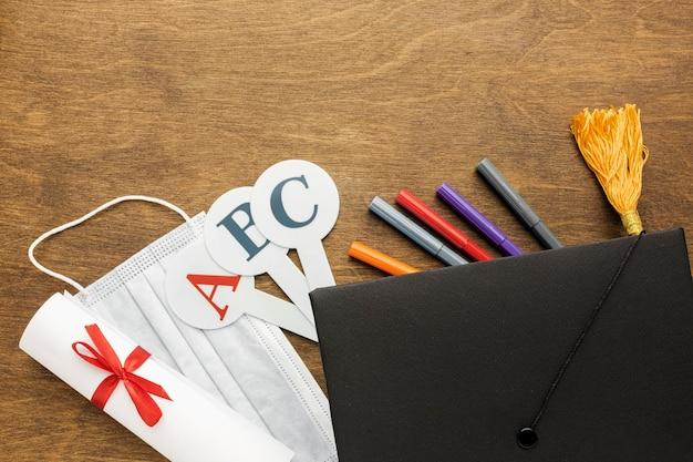 Вид сверху академической шапки со школьными принадлежностями и медицинской маской