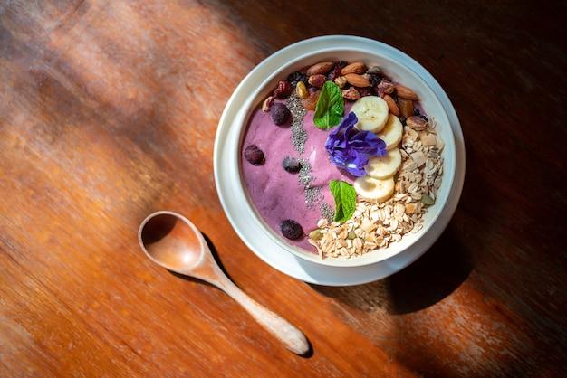 ブルーベリースムージー、新鮮なバナナ、ベリー、ヒマワリの種、ミントと蝶のエンドウ豆とチアシードを混ぜたアサイーボウルの上面図。健康でビーガニズムの人々のためのビーガン朝食ボウル。