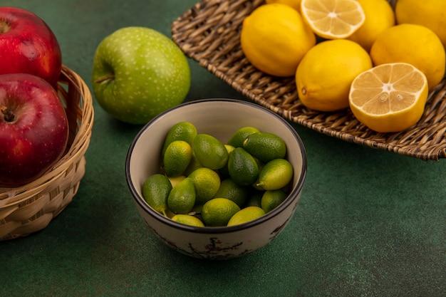 緑の表面のバケツに赤い甘いリンゴとボウルにキンカンと籐のトレイに酸風味のレモンの上面図
