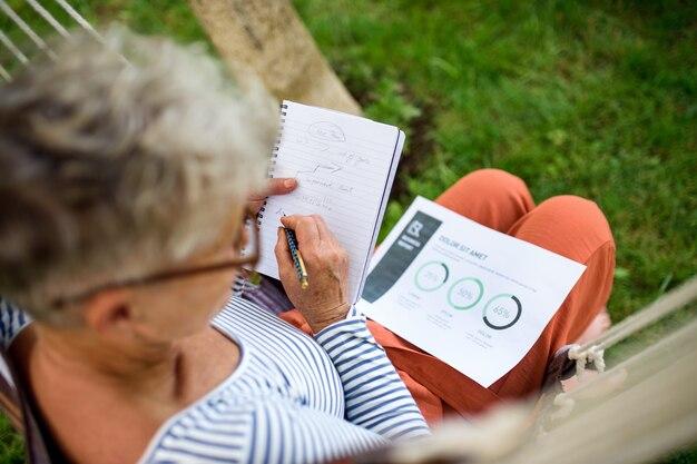 Вид сверху активной старшей женщины, работающей на открытом воздухе в саду, концепции зеленого домашнего офиса.
