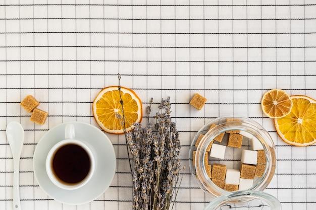 市松模様のテーブルクロスにお茶と砂糖のボウルのカップの上面図