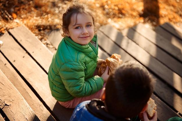 緑のジャケットを着て、焼きたてのおいしいクロワッサンを手に兄の隣に座っているカメラを見て、秋の自然の背景で屋外で朝食を楽しんでいる愛らしい女の赤ちゃんの上面図