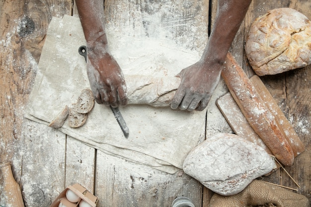 アフリカ系アメリカ人の男の上面図は、木製のテーブルで新鮮なシリアル、パン、ふすまを調理します。おいしい食事、栄養、工芸品。グルテンフリー食品、健康的なライフスタイル、オーガニックで安全な製造。手作り。