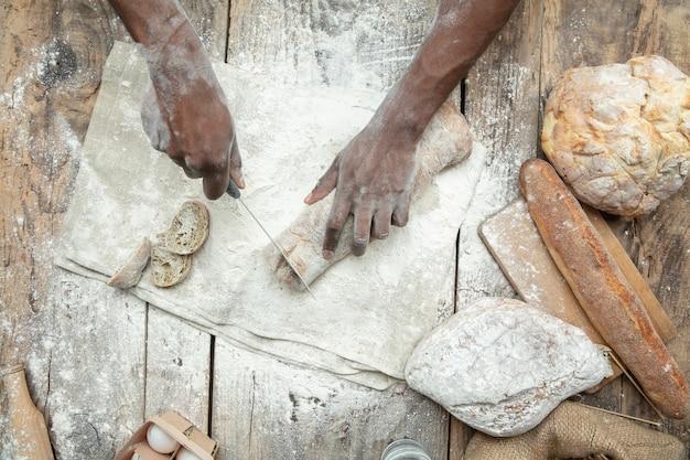 아프리카 계 미국인 남자의 상위 뷰는 나무 테이블에 신선한 시리얼, 빵, 밀기울을 요리합니다. 맛있는 식사, 영양, 공예품. 글루텐 프리 식품, 건강한 생활 방식, 유기농 및 안전한 제조. 수공.