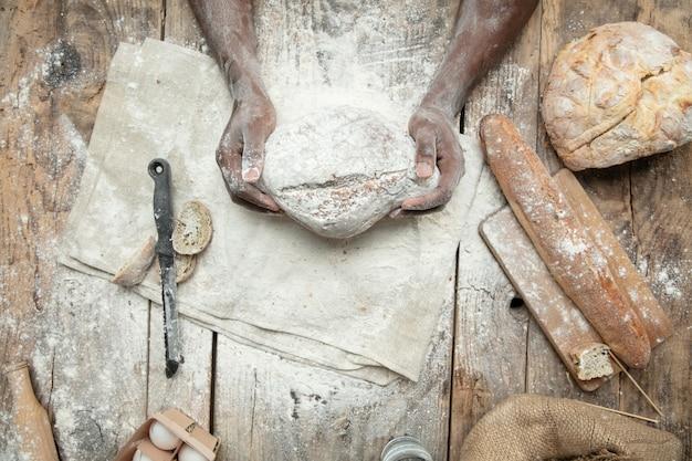 아프리카 계 미국인 남자의 상위 뷰는 나무 테이블에 신선한 시리얼, 빵, 밀기울을 요리합니다. 맛있는 먹거리, 영양, 공예품