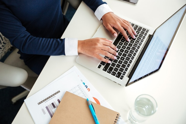オフィスでラップトップを使用してドレスを着たアフリカのビジネス女性の平面図です。トリミングされた画像