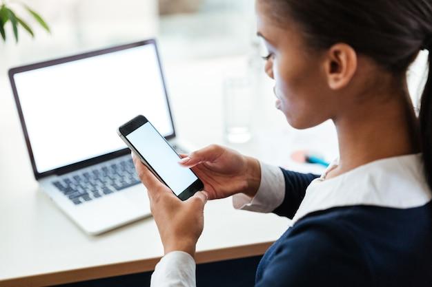 ノートパソコンとテーブルのそばに座って、オフィスで電話を使用してドレスを着たアフロビジネス女性の平面図です。トリミングされた画像。