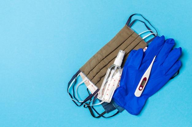 파란색 표면에 알코올 손 소독제, 라텍스 장갑, 디지털 온도계 및 수제 재사용 가능한 마스크의 상위 뷰