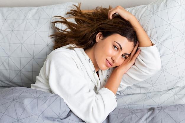 Вид сверху очаровательной женщины в постели в пижаме