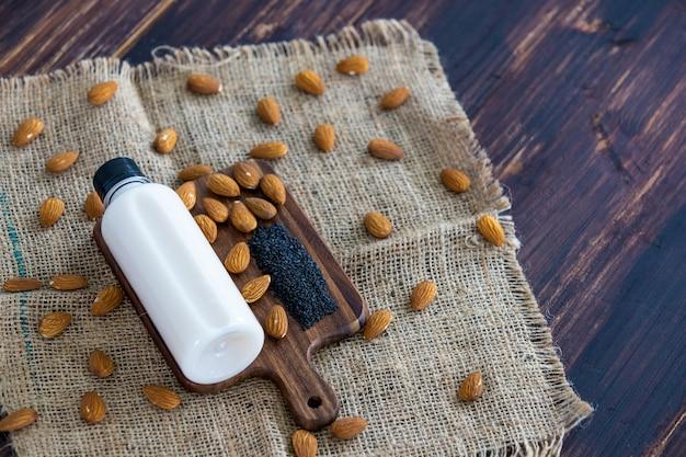素朴な生地の木製トレイとテーブルにアーモンドナッツとゴマの種が入ったプラスチックボトルに入ったゴマ入りアーモンドミルクの上面図。代替の有機健康デトックスとダイエット食品および飲料の概念。