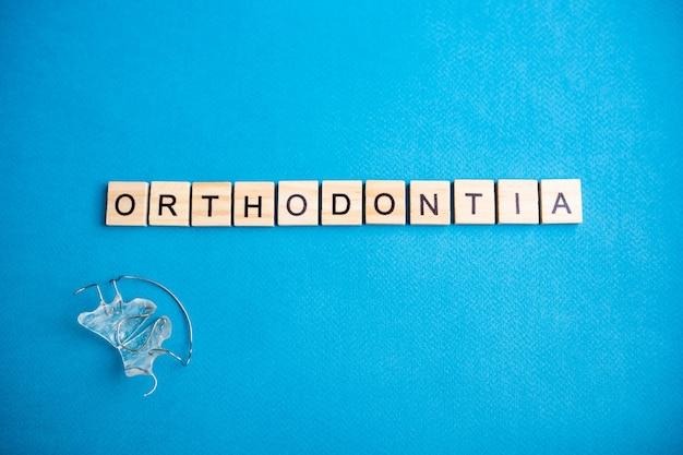 파란색 배경에 글자와 알파벳 블록의 상위 뷰. 치열 교정-레터링. 치아의 윗줄에 대한 문자 및 교정 장치