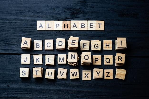 검은 나무 바탕에 글자와 알파벳 블록의 최고 볼 수 있습니다. 알파벳-비문 및 문자 그룹.
