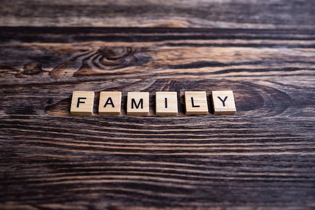 갈색 나무 바탕에 글자와 알파벳 블록의 최고 볼 수 있습니다. 비문 가족.