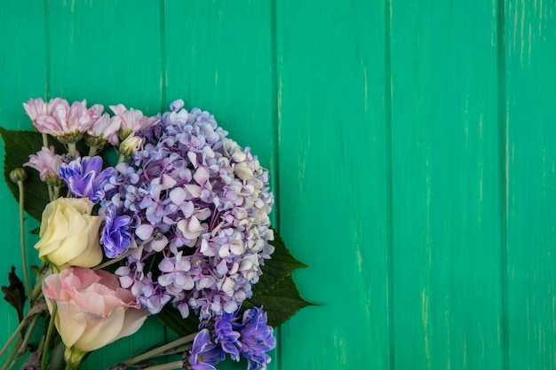 コピースペースと緑の木製の背景にgardenziaデイジーローズのような驚くべきカラフルな花の上面図