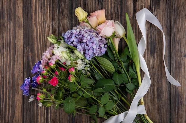 木製の背景に白いリボンの葉とライラックバラデイジーなどの素晴らしい花の上面図