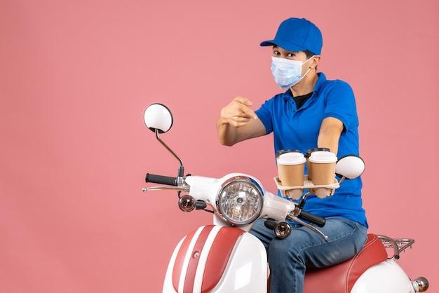 Вид сверху амбициозного курьера в маске в шляпе, сидящего на скутере и показывающего заказы на пастельно-персиковом фоне