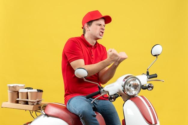 黄色の背景に注文を配信赤いブラウスと帽子を身に着けている野心的な感情的な若い男の上面図