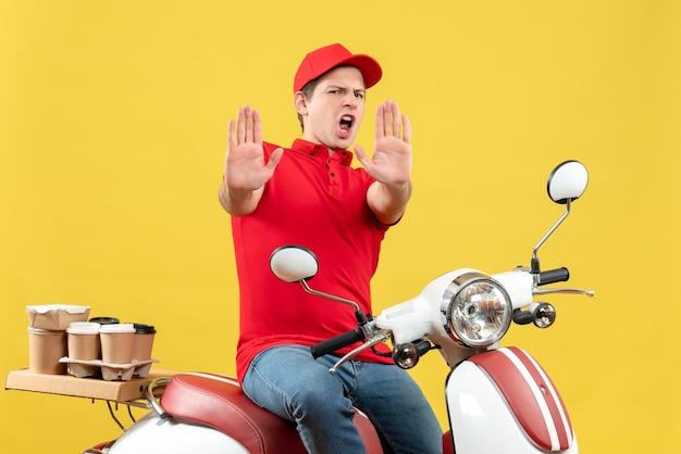 赤いブラウスと帽子をかぶって、黄色の背景に10を示す注文を配信する野心的な感情的な若い男の上面図