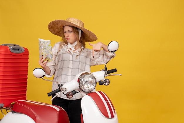 バイクに座って、okジェスチャーを作る地図を保持している彼女の荷物を収集する帽子をかぶっている野心的な若い女性の上面図