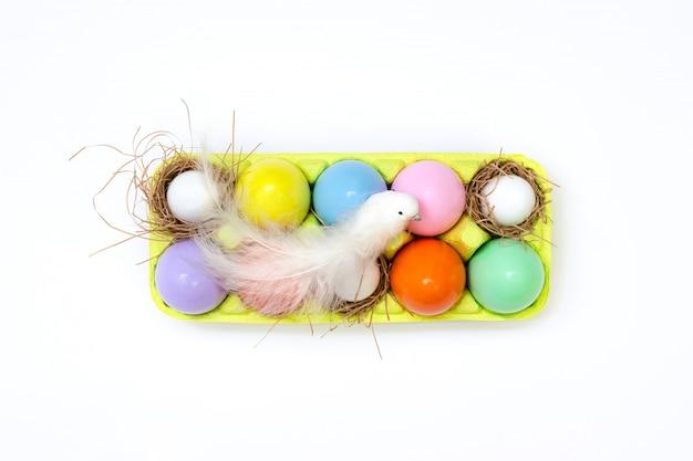 コンテナー内の明るいジューシーな色で塗られた卵のイースター組成物の平面図と白い鳥が上に座っています。