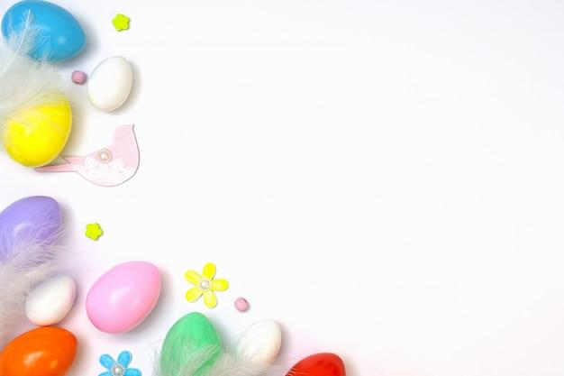 白い鳥の羽と花と白い背景に明るいジューシーな色で塗られた卵のイースター組成の平面図