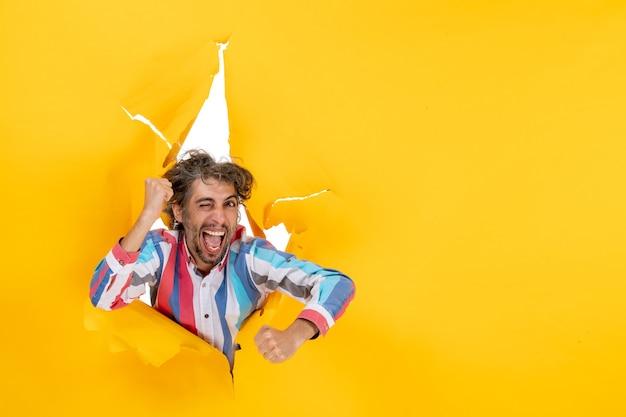 노란 종이에 찢어진 구멍을 통해 카메라를 위해 포즈를 취하는 감정적이고 미친 젊은 남자의 상위 뷰