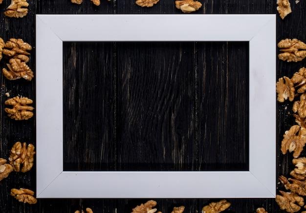 Взгляд сверху пустой картинной рамки с грецкими орехами на деревянном