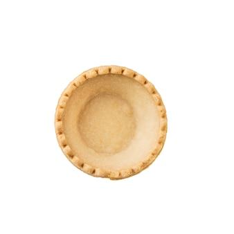 白い表面に分離された空のタルトの上面図。おやつ用の焼き菓子。