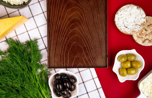 Вид сверху пустой деревянный поднос и сыр с маринованными оливками и рисовые лепешки на клетчатой ткани на красном