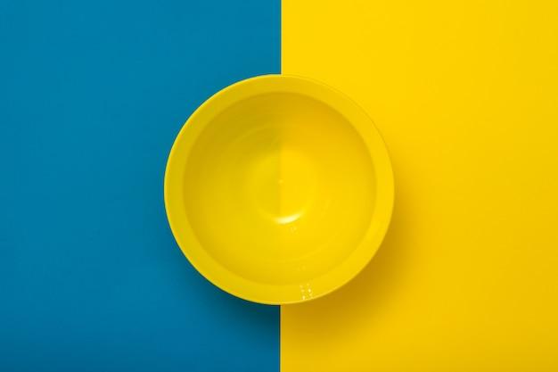 노란색과 파란색 배경에 빈 노란색 그릇의 상위 뷰. 주방용 플라스틱 기구.