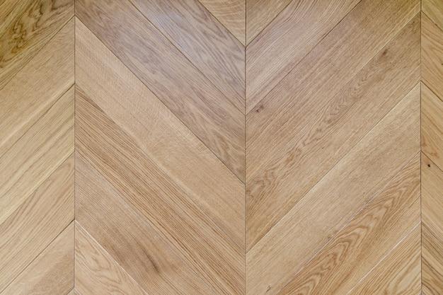 自然光の下でのフレンチ ヘリンボーンの寄せ木張りの床の平面図。オークの斜めのテクスチャーを持つ木の模様。
